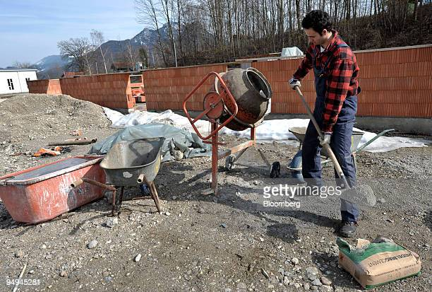 A construction worker uses a shovel to scoop from a bag of HeidelbergCement on a construction site near Rosenheim Germany on Friday March 13 2009...