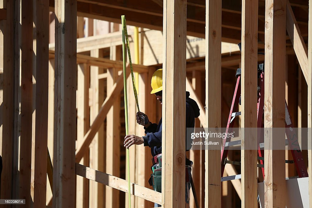 A construction worker uses a tape measure to take a measurement at a new housing development on February 20, 2013 in San Mateo, California. The Commerce Department reported that new housing starts dropped 8.5% in January following a 15.7% increase one month earlier.