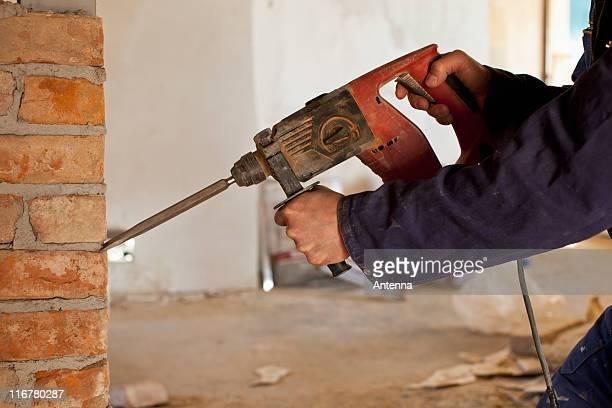 A construction worker using a jackhammer drill