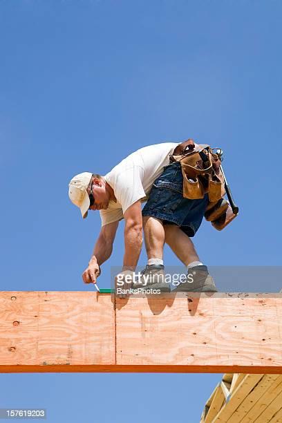 Travailleur de la Construction en utilisant un débit mètres sur sandale poutres en bois