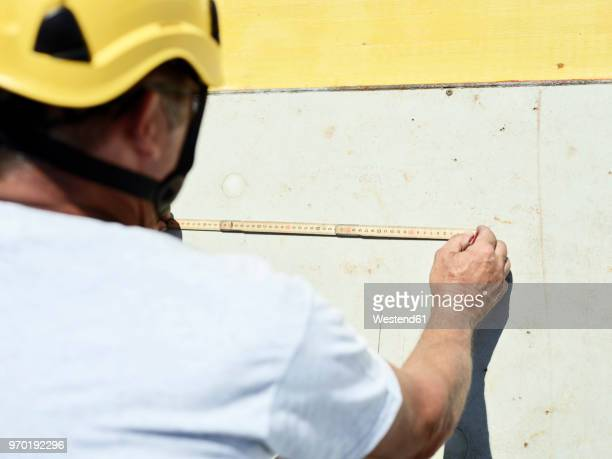 Construction worker using folding ruler and pencil on concrete wall