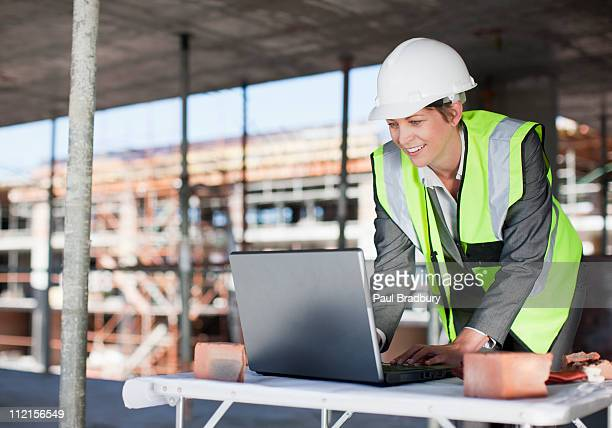 Construction worker using laptop on construction site