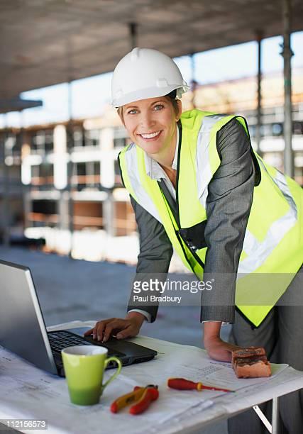 Trabalhador da Construção Civil com computador portátil no local de Construção