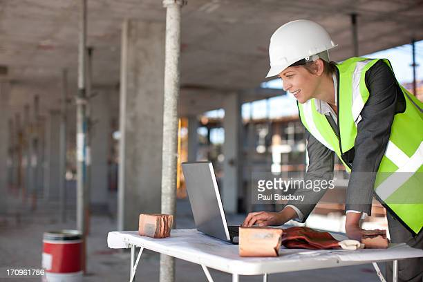 construction worker using laptop on construction site - building contractor stock pictures, royalty-free photos & images