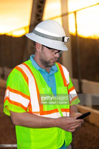 construction worker using mobile phone while standing during sunset - florin seitan stock pictures, royalty-free photos & images