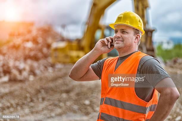 Trabajador de la construcción mediante teléfono inteligente