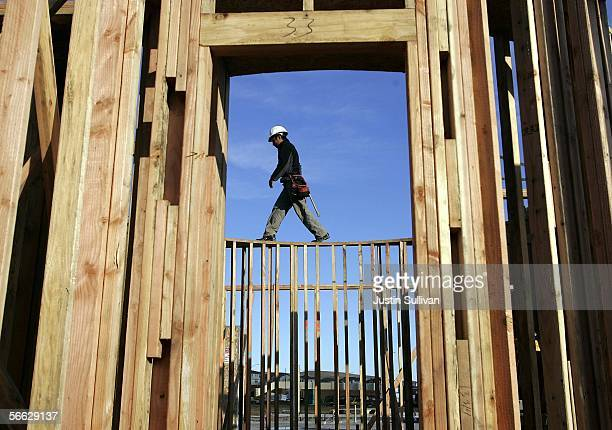 A construction worker walks across the framing on a new home under construction January 19 2006 in Dublin California The Commerce Department reported...