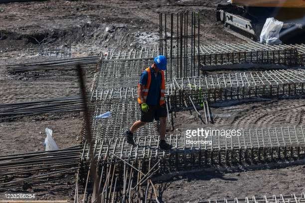 Construction worker walks on steel reinforcement rods on the new Smichov City district building project, on a plot of brownfield land in Prague,...