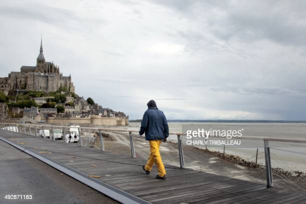 A construction worker walks on the MontSaintMichel's new bridge construction site on May 22 2014 The MontSaintMichel a French landmark and UNESCO...