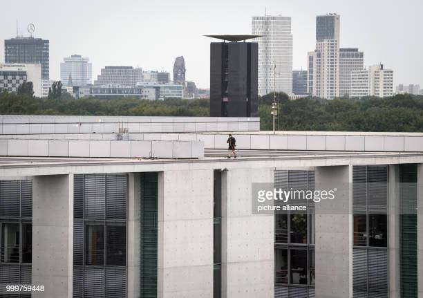 A construction worker walks on top of the Paul Loebe House in Berlin Germany 8 September 2017 Beyond him the Carillon glockenspiel tower the Europa...