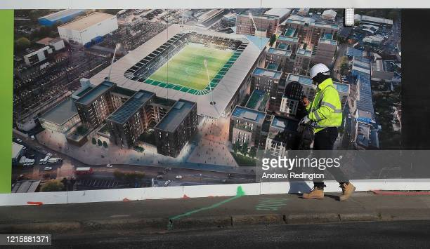 Construction worker walks past an artist's impression of the under construction Plough Lane stadium of AFC Wimbledon on March 31, 2020 in London,...
