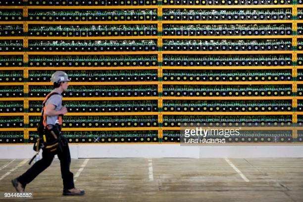 A construction worker walks past bitcoin mining at Bitfarms in Saint Hyacinthe Quebec on March 19 2018 Bitcoin is a cryptocurrency and worldwide...