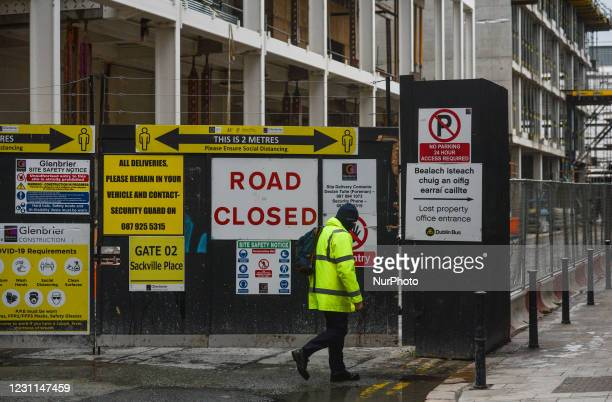 Construction worker walks past signs and signage attached to the entrance gate in Dublin city center, during Level 5 Covid-19 lockdown. On Saturday,...