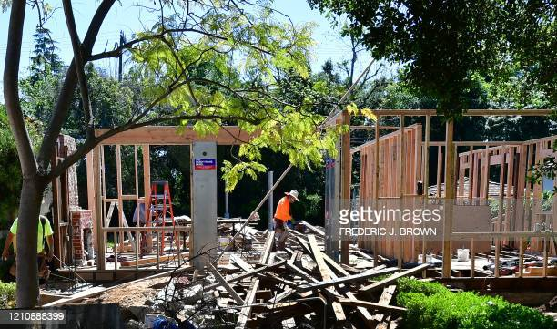 A construction worker walks through a site of a new house being built in San Marino California on April 24 2020 The coronavirus pandemic has worsened...