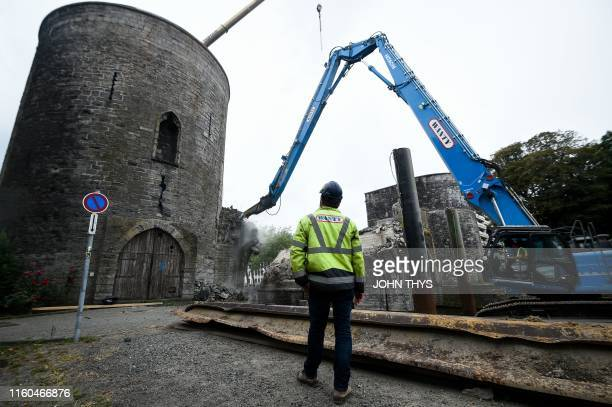 "Construction worker watches as the ""Pont des Trous"" medieval bridge is being demolished by a crane in Tournai, where the Scheldt river will be..."