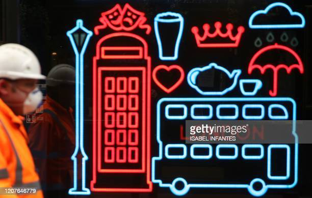 A construction worker wearing a face mask passes a neon display in the window of a shop in London on March 19 2020 as efforts continue to delay the...