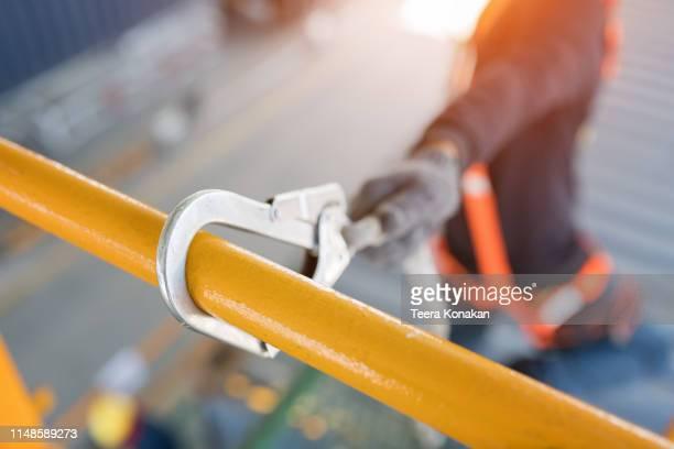construction worker wearing safety harness and safety line working at high place - alto posición descriptiva fotografías e imágenes de stock
