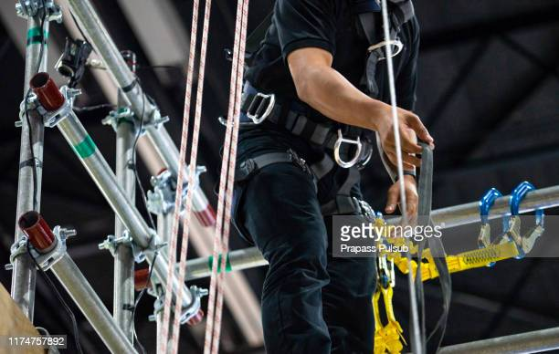 construction worker wearing safety harness and safety line working at high place - safety harness stock pictures, royalty-free photos & images