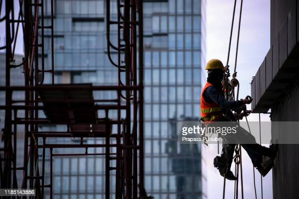 construction worker wearing safety harness and safety line working at high place - safety equipment stock pictures, royalty-free photos & images