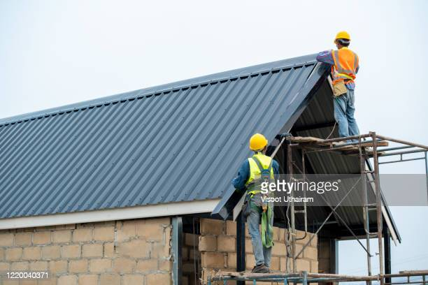 construction worker wearing safety harness are working on the roof house. - culebrilla enfermedad fotografías e imágenes de stock