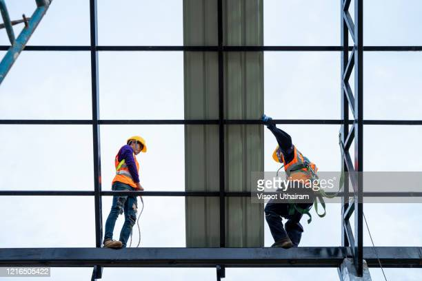 construction worker wearing safety harness belt during working installing new roof. - ベルト ストックフォトと画像
