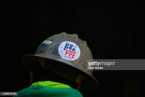 """Construction worker wears a """" Pull Up & Vote"""" sticker on his hard hat as voters queue outside of Philadelphia City Hall to cast their early voting..."""