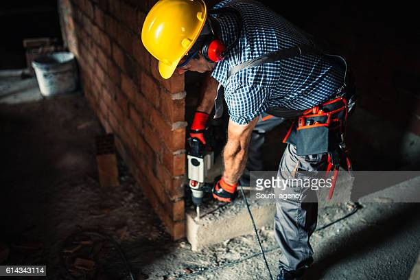 Construction worker with a drill