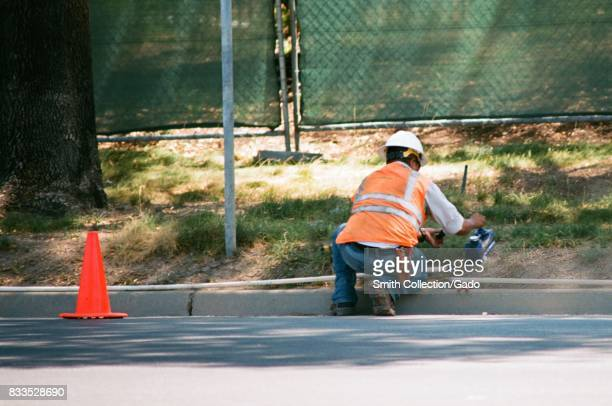 A construction worker with a high visibility vest installs PVC piping at the Apple Park known colloquially as 'The Spaceship' the new headquarters of...