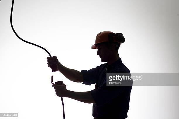 A construction worker with an electric cable.