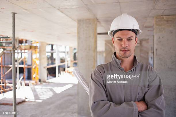 Construction worker with arms crossed on construction site