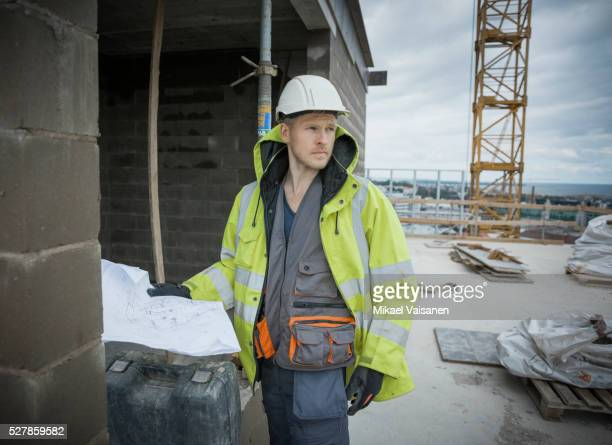 Construction worker with blueprints on high rise site