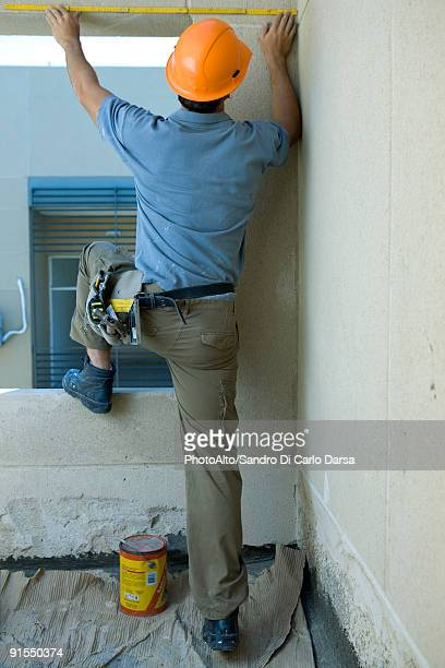 Construction worker with foot on windowsill measuring space above window