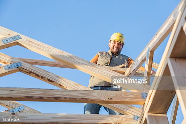 Construction worker with hammer on roof of house frame