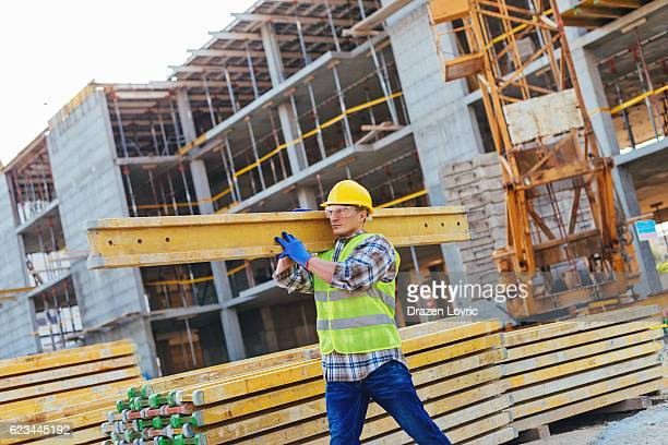Construction worker with hardhat carrying planks
