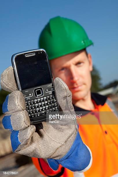 Bauarbeiter mit Smartphone in der hand.