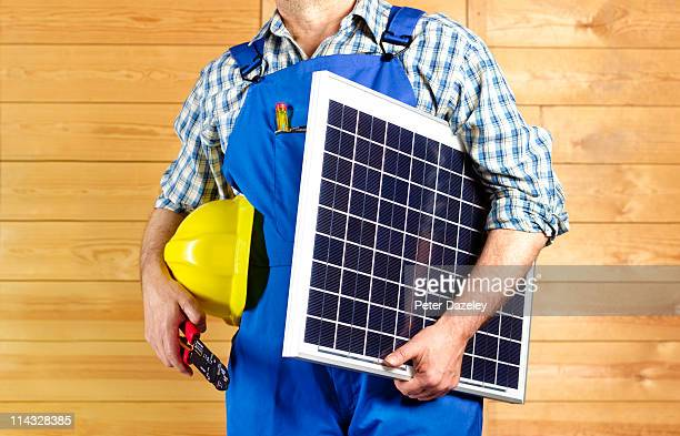 construction worker with solar panel - newpremiumuk stock pictures, royalty-free photos & images