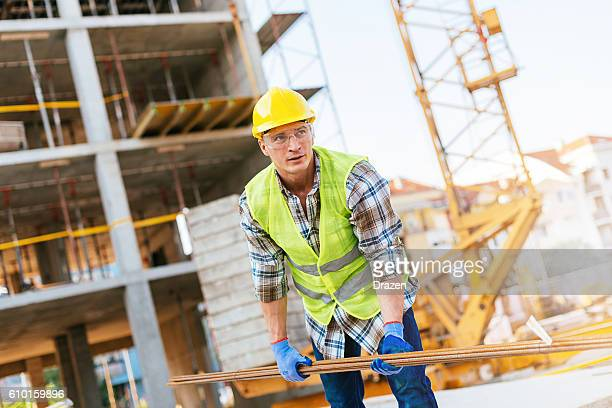 Construction worker with steel rods under the crane