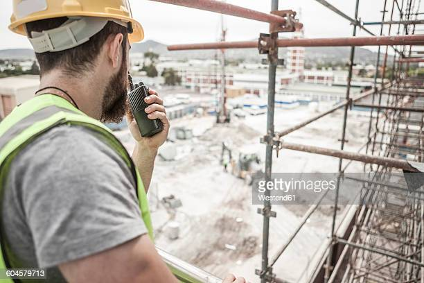 Construction worker with walkie-talkie in construction site