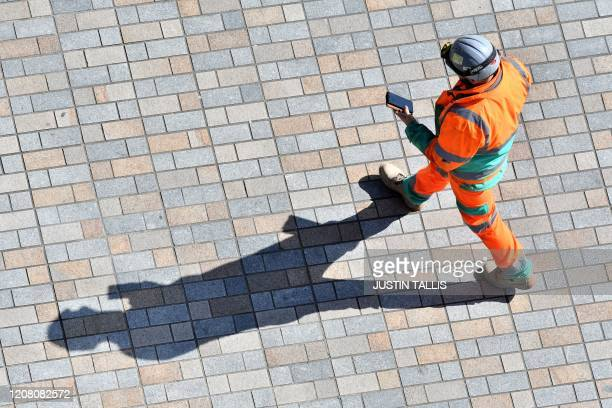 A construction worker working on the Thames Tideway scheme walks in south London on March 24 as Britain's Chancellor of the Duchy of Lancaster...