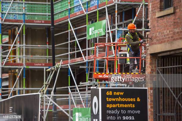 Construction worker works from a cherry picker on the South Bank development beside the Liverpool and Leeds Canal in Leeds, U.K., on Wednesday, Feb....