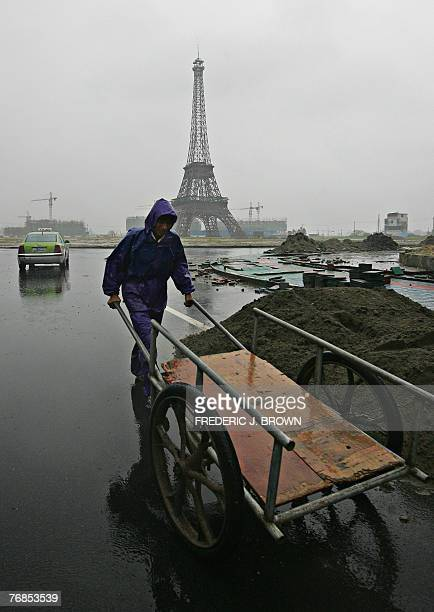 A construction worker works in the rain near a replica of the Eiffel Tower at a commercial and residential project resembling a miniParis being built...
