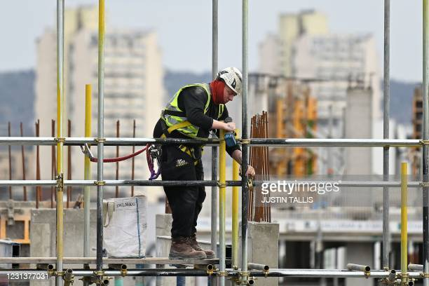 Construction worker works to build new apartments and a retail complex at Nine Elms in south London on February 25 as building sites remain open...