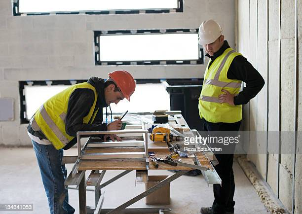 Construction worker writes on work order