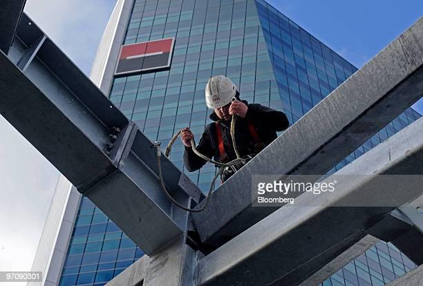 Construction worker Yohan Lellandais checks Ibeams on a Vinci SA construction site in front of the Societe Generale headquarters at La Defense in...