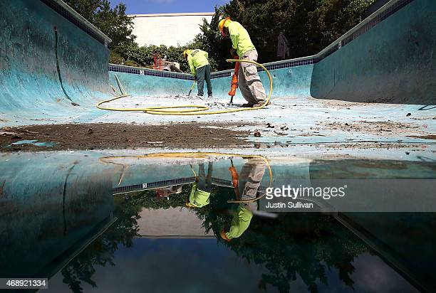 Construction workers Alex Hernandez and Raul Buenrostro begin demolition of a swimming pool at an apartment complex on April 8 2015 in Hayward...
