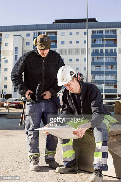 Construction workers analyzing blueprint at site
