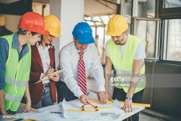 Construction workers and architects looking at blueprints