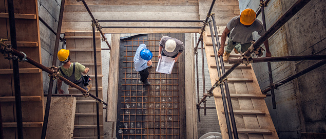 Construction workers and architects viewed from above 646587338