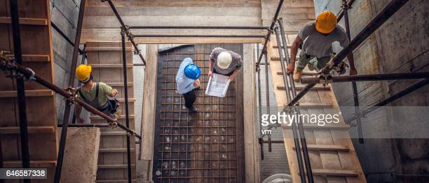 Construction workers and architects viewed from above