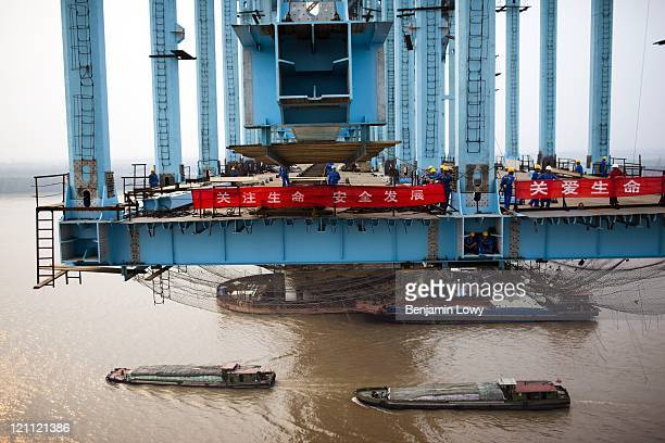 Construction workers are in the process of laying railroad bridge for the Chinese high speed rail network on July 3, 2009 in Nanjing, China. The...